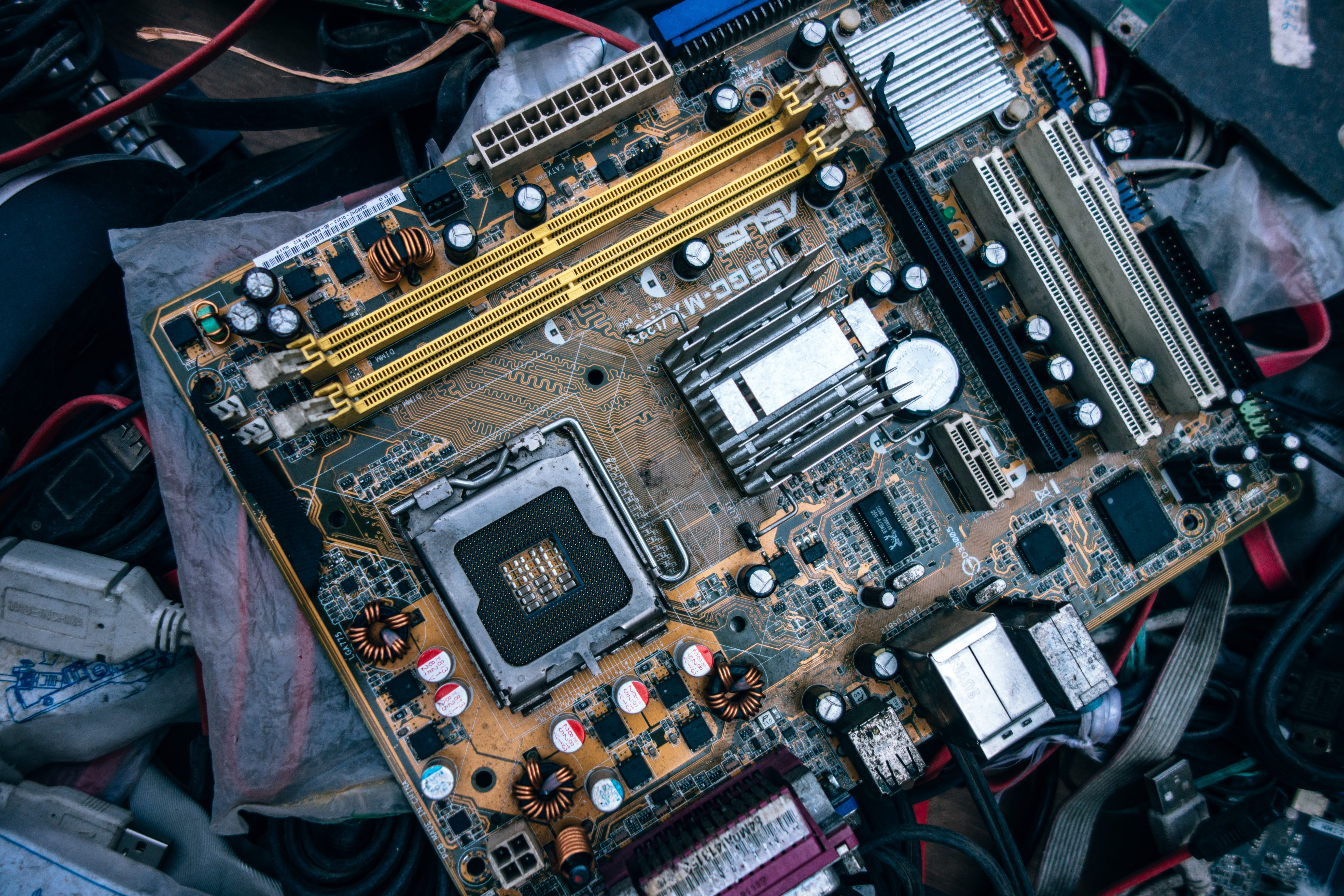 A computer Motherboard in a pile of other parts